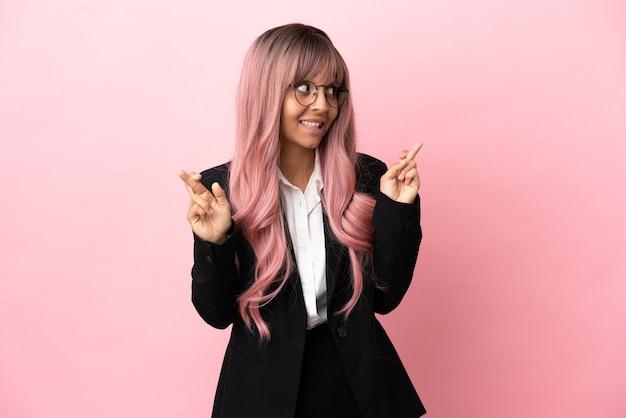 Giovane donna di razza mista d'affari con i capelli rosa isolata su sfondo rosa con le dita incrociate