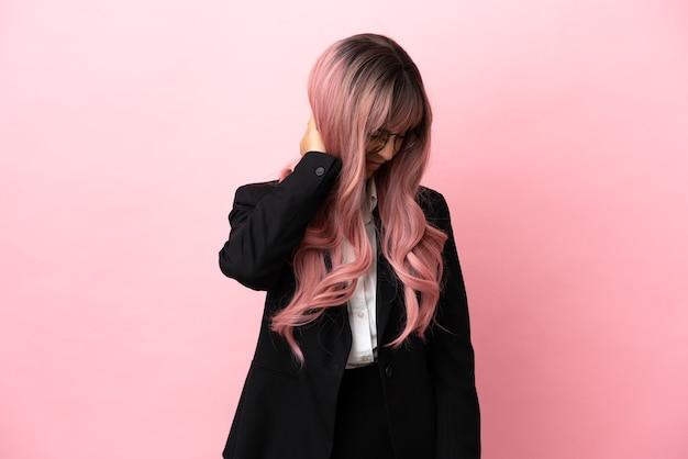 Giovane donna di razza mista d'affari con i capelli rosa isolata su sfondo rosa con mal di collo