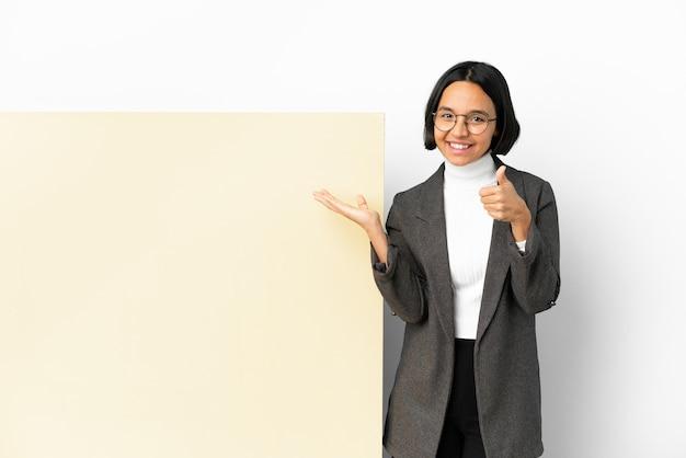 Young business razza mista donna con con un grande banner su sfondo isolato tenendo copyspace immaginario sul palmo per inserire un annuncio e con il pollice in alto