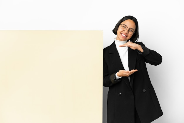 Giovane donna di razza mista d'affari con un grande banner su sfondo isolato che tiene copyspace immaginario sul palmo per inserire un annuncio