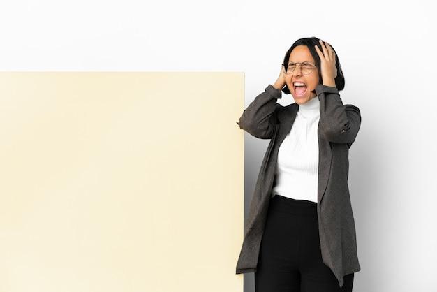 Giovane donna di razza mista con un grande striscione su sfondo isolato stressata sopraffatta over