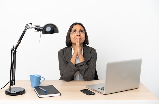 La donna della corsa mista di giovane impresa che lavora all'ufficio tiene insieme la palma. la persona chiede qualcosa