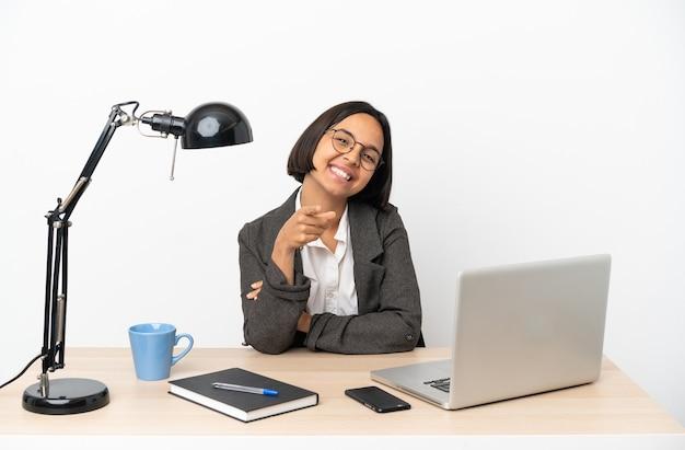Young business donna di razza mista che lavora in ufficio che punta davanti con felice espressione