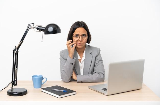 Giovane donna d'affari di razza mista che lavora in ufficio mostrando un segno di gesto di silenzio