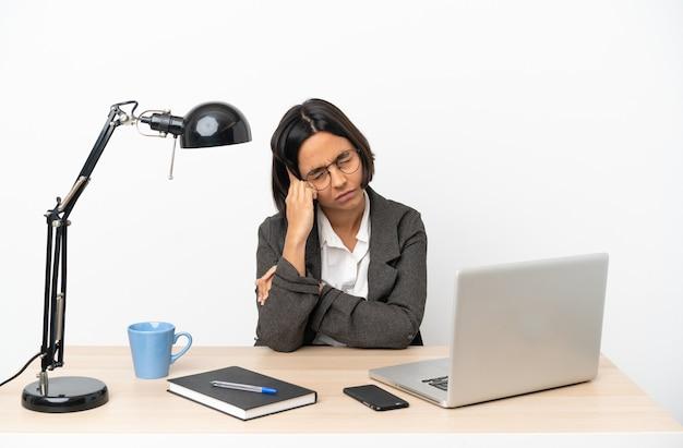 Giovane donna d'affari di razza mista che lavora in ufficio con mal di testa