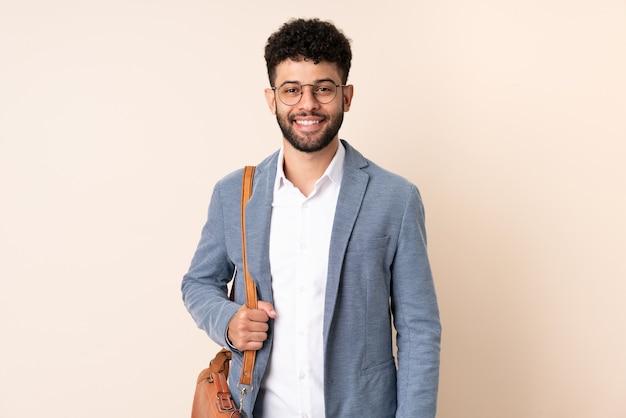 Giovane uomo d'affari marocchino isolato su sfondo beige mantenendo le braccia incrociate in posizione frontale
