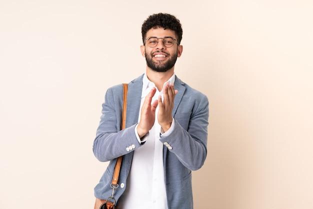 Giovane uomo marocchino di affari isolato sulla parete beige che applaude dopo la presentazione in una conferenza