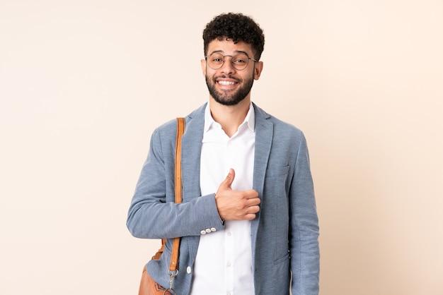 Giovane uomo marocchino di affari isolato sulla parete beige che dà un pollice in alto gesto