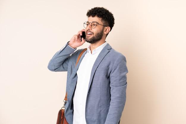 Giovane uomo marocchino di affari isolato sulla parete beige mantenendo una conversazione con il telefono cellulare