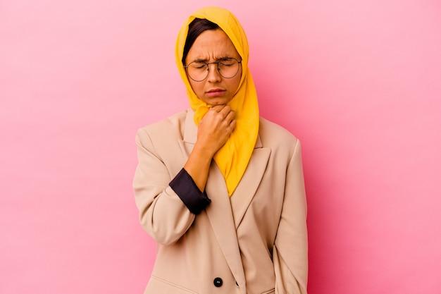 Una giovane donna musulmana d'affari isolata su sfondo rosa soffre di dolore alla gola a causa di un virus o di un'infezione.
