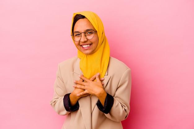 Giovane donna musulmana di affari isolata sulla parete rosa ride ad alta voce mantenendo la mano sul petto