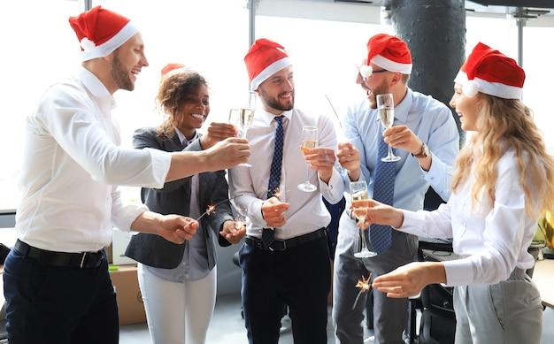 Giovani soci in affari accendono luci del bengala e bevono champagne in un ufficio moderno. buon natale e felice anno nuovo.