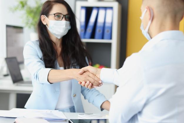 I giovani uomini d'affari in maschere mediche si stringono la mano al tavolo di lavoro