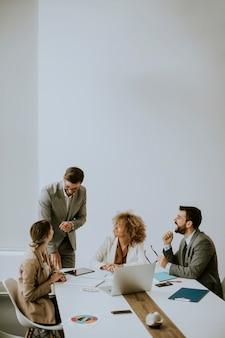 Giovani imprenditori seduti al tavolo della riunione nella sala conferenze discutendo il lavoro e la strategia di pianificazione
