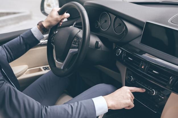 Giovane uomo d'affari prova un nuovo lettore musicale per veicoli