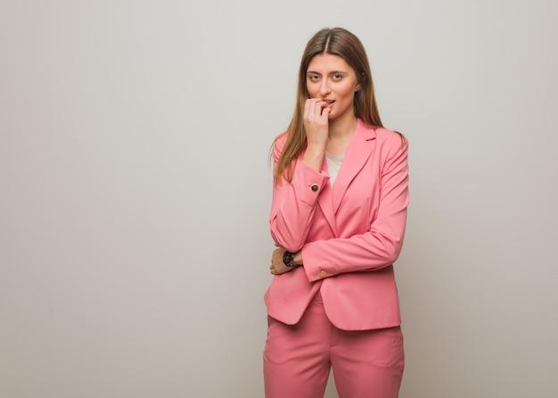 Giovane ragazza russa di affari che si morde le unghie, nervosa e molto ansiosa