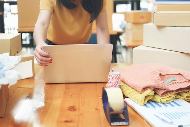 Proprietario di un venditore online di avvio di una giovane azienda che utilizza il computer per controllare gli ordini dei clienti da e-mail o sito web e preparare i pacchetti per le apparecchiature per ufficio del prodotto.
