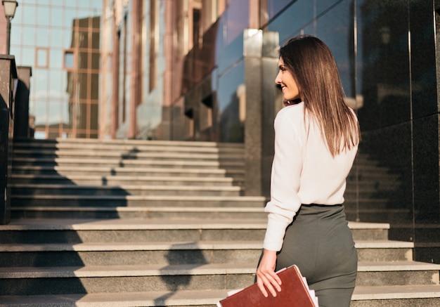 Giovane donna d'affari in una camicetta e una gonna sta parlando al telefono.