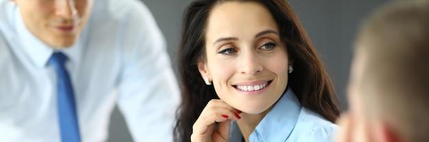 La giovane donna di affari in camicia blu comunica con due uomini nel ritratto dell'ufficio. trattative con il cliente e conclusione del concetto di transazioni.