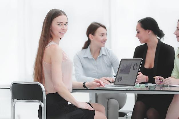 Giovane donna d'affari e colleghi a una riunione di lavoro in ufficio