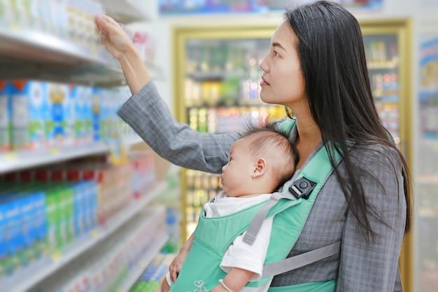 Giovane donna d'affari nel negozio di alimentari mentre portava il suo bambino da baby carrie ergonomica