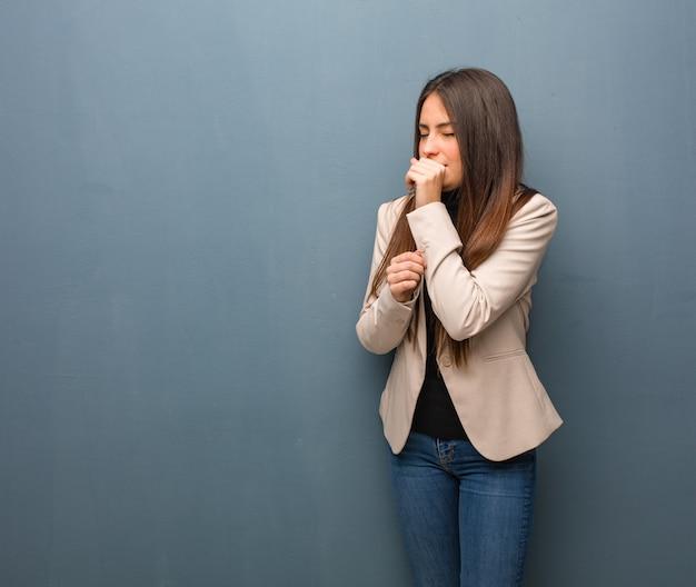 Giovane donna d'affari che tossisce, malata a causa di un virus o di un'infezione