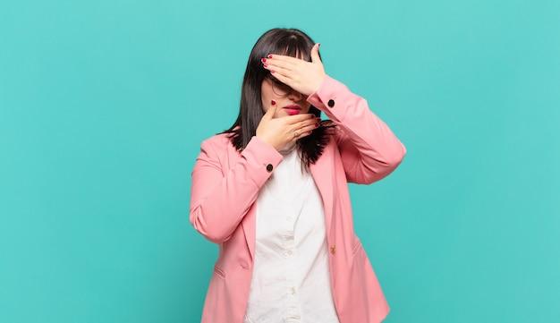 Giovane donna d'affari che copre il viso con entrambe le mani dicendo no alla telecamera! rifiutare le foto o vietare le foto