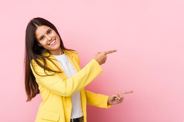 Giovane donna d'affari eccitato indicando con gli indici di distanza.