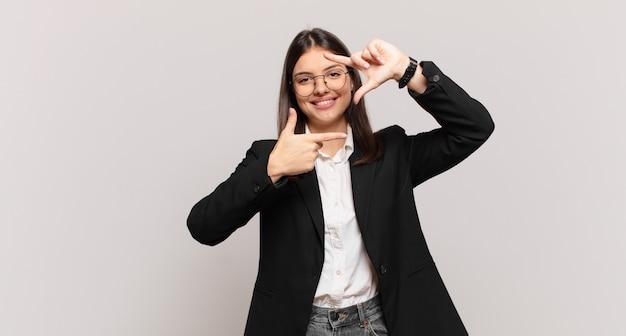 Giovane donna d'affari che si sente felice, amichevole e positiva, sorride e fa un ritratto o una cornice per foto con le mani
