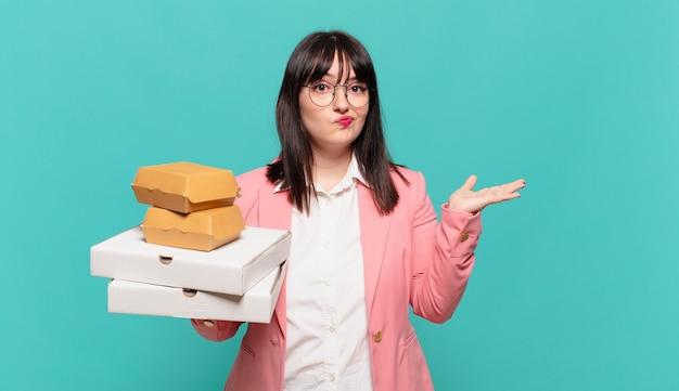 Giovane donna d'affari che si sente perplessa e confusa, dubitando, ponderando o scegliendo diverse opzioni con un'espressione divertente