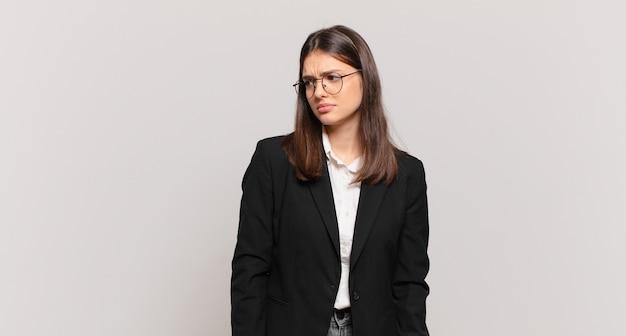 Giovane donna d'affari che si sente triste, turbata o arrabbiata e guarda di lato con un atteggiamento negativo, accigliata in disaccordo