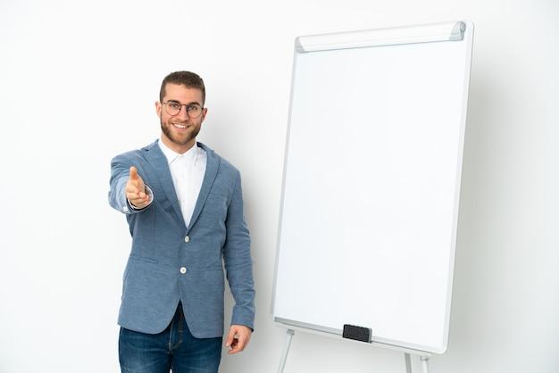Giovane donna d'affari che dà una presentazione sulla lavagna bianca isolata su sfondo bianco stringe la mano per la chiusura di un buon affare