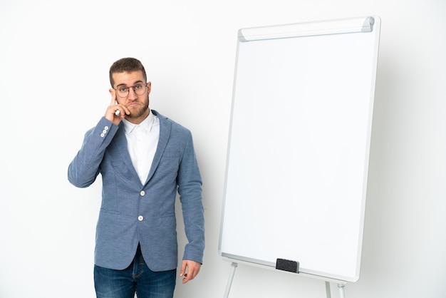 Giovane donna d'affari che fa una presentazione su una lavagna bianca isolata su sfondo bianco pensando a un'idea
