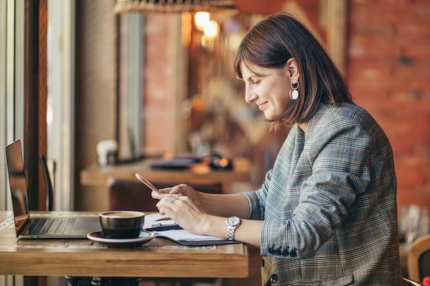 Giovane donna d'affari in giacca grigia che utilizza smartphone e lavora su net-book, seduta al bar vicino alla finestra con caffè. accogliente mattina autunnale o invernale.