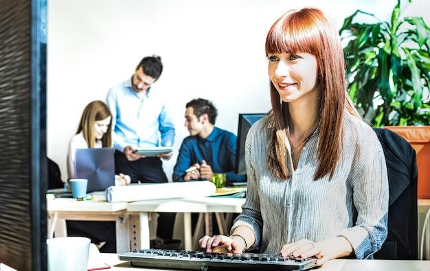 Giovane donna d'affari che si diverte a lavorare al computer con i colleghi alla riunione d'ufficio - moderno concetto di avvio di impegno connesso con un atteggiamento produttivo felice - filtro di contrasto vivido brillante