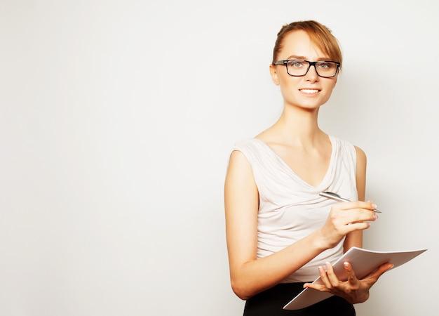 Giovane donna d'affari tenere pagine di carta.