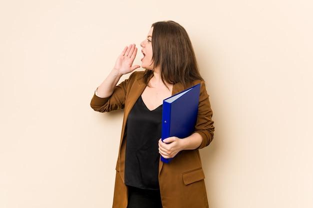 Giovane donna di affari che tiene file gridando e tenendo il palmo vicino alla bocca aperta.