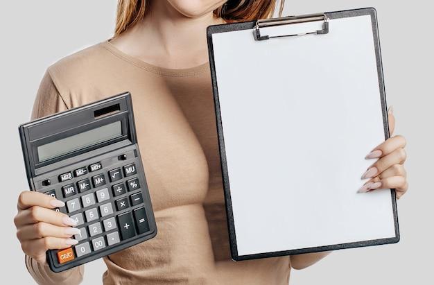 La giovane donna di affari tiene la calcolatrice e la lavagna per appunti con derisione sullo spazio vuoto isolato su spazio grigio