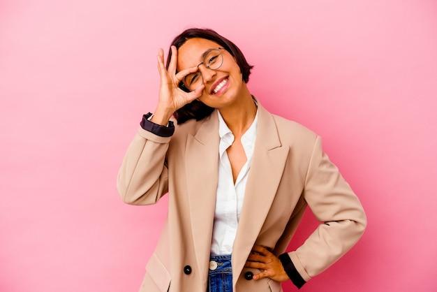 La giovane donna di affari isolata sulla parete rosa ha eccitato mantenendo il gesto giusto sull'occhio