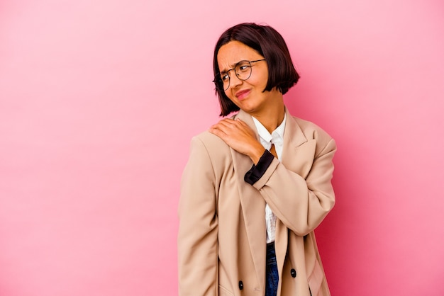 Giovane donna di affari isolata sulla parete rosa che ha un dolore alla spalla