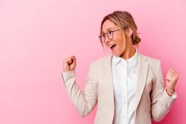 Giovane donna di affari isolata sulla parete rosa che alza il pugno dopo una vittoria