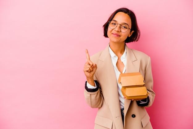 Giovane donna di affari isolata sulla parete rosa che mostra il numero uno con il dito