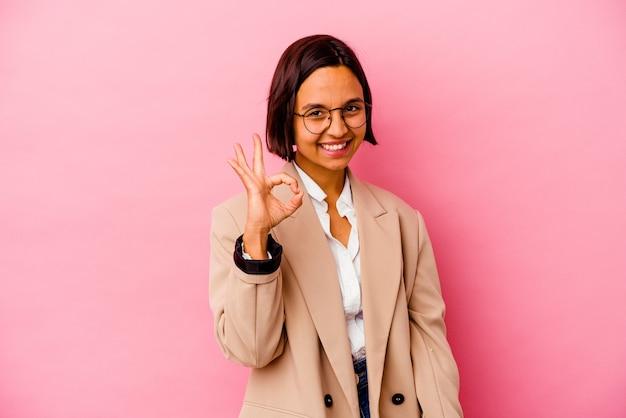 La giovane donna di affari isolata sulla parete rosa strizza l'occhio e tiene un gesto giusto con la mano