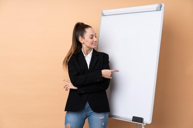 Giovane donna di affari sopra la parete isolata che dà una presentazione sul bordo bianco e che lo indica