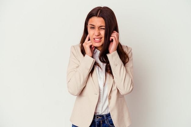 Giovane donna di affari isolata sul muro bianco che copre le orecchie con le mani