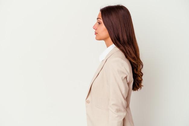 Giovane donna di affari isolata sulla parete bianca che guarda a sinistra, posa lateralmente