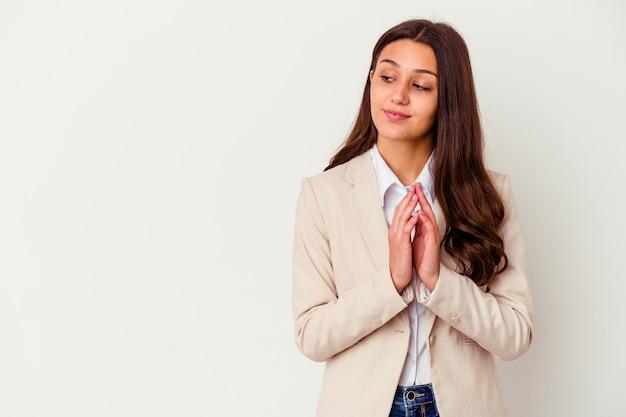Giovane donna d'affari isolata sul muro bianco che compongono il piano in mente, la creazione di un'idea