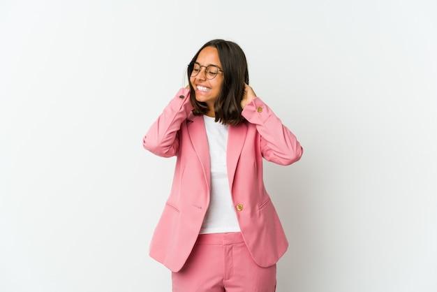 Giovane donna di affari isolata sul muro bianco che grida eccitato alla parte anteriore