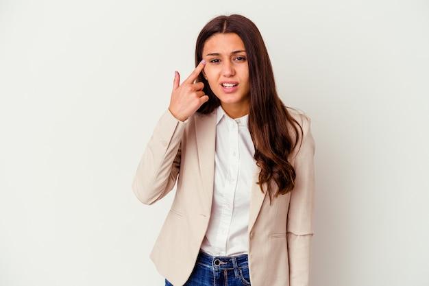 Giovane donna di affari isolata sulla parete bianca che mostra un gesto di delusione con l'indice