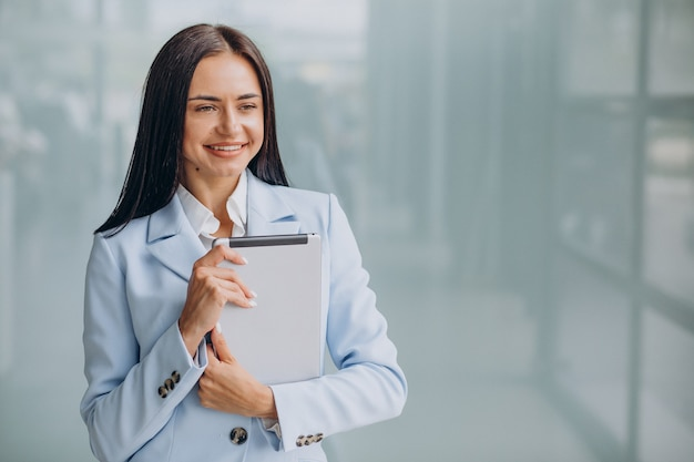 Giovane donna d'affari isolata tenendo il tablet